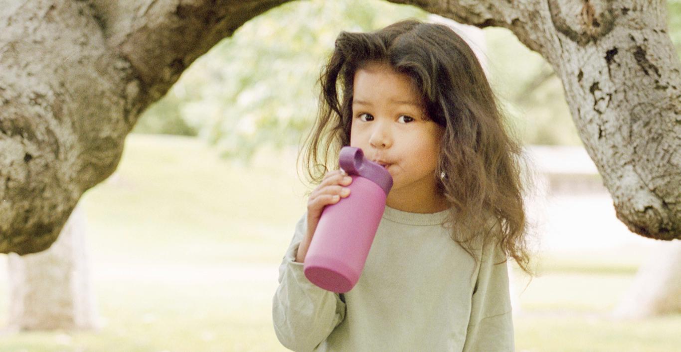 Girl drinking purple PLAY tumbler