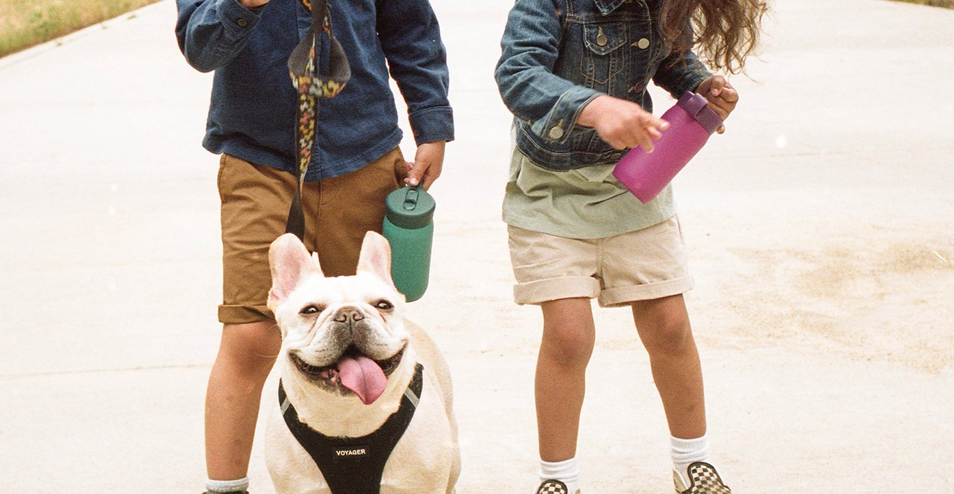 Two children holding the PLAY tumbler and a dog