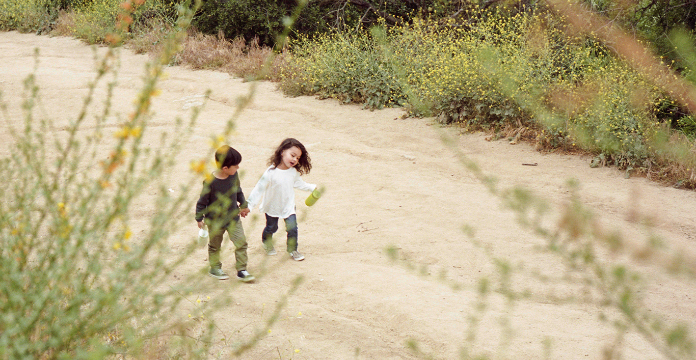 Two children walking up a dirt road