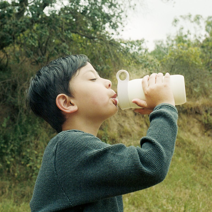 Little boy drinking out of the white PLAY tumbler
