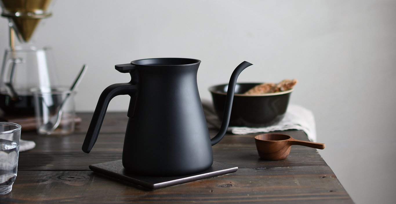 POUR OVER KETTLE black placed on a coaster with tableware