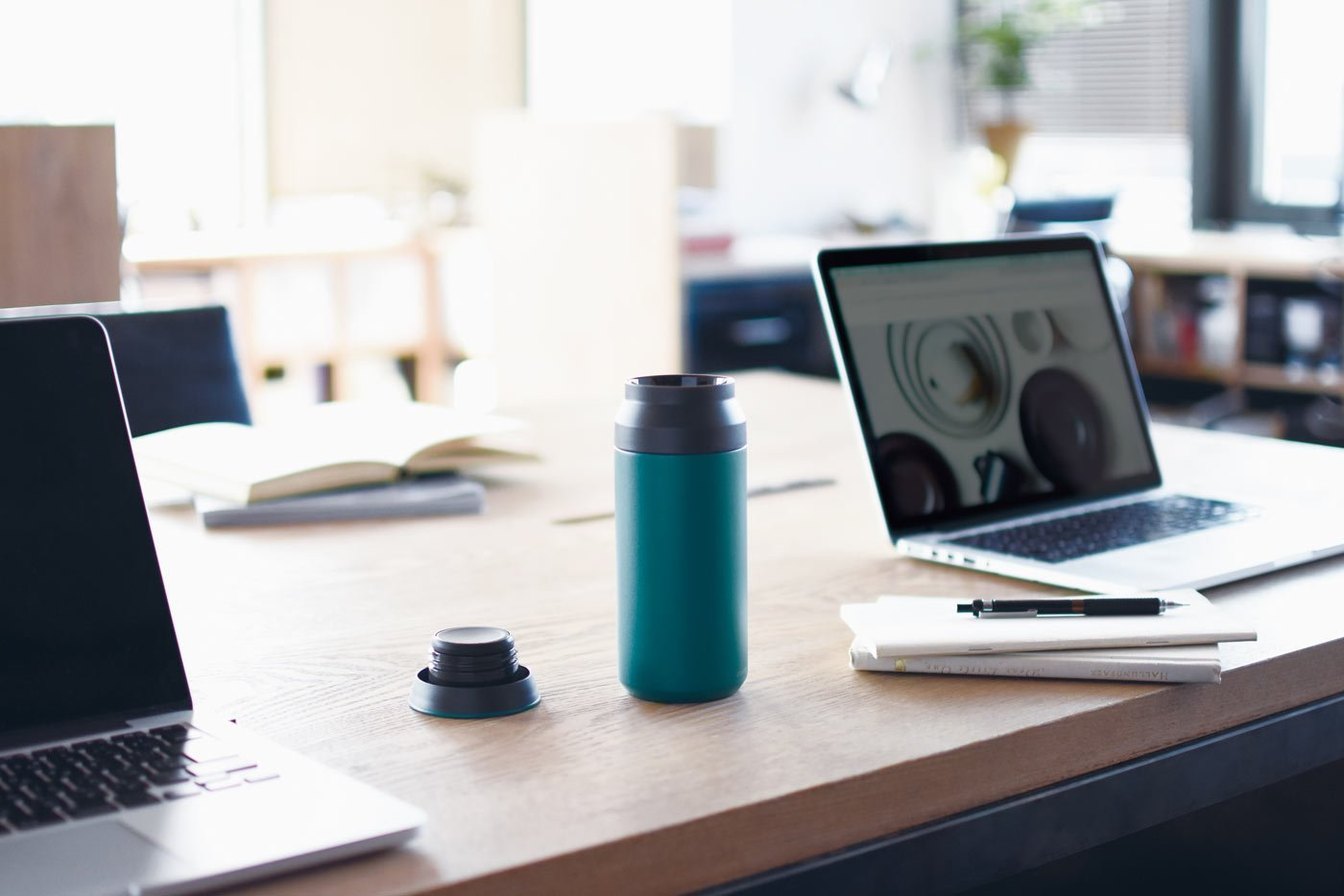 TRAVEL tumbler 500ml in turquoise on a desk with laptops