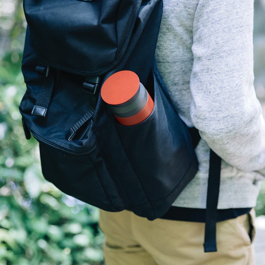 TRAVEL tumbler in red on the side pouch of a backpack