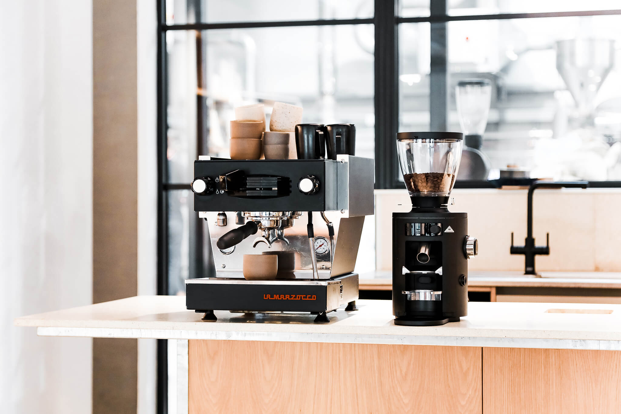 A home espresso machine and home coffee grinder sitting on a bar