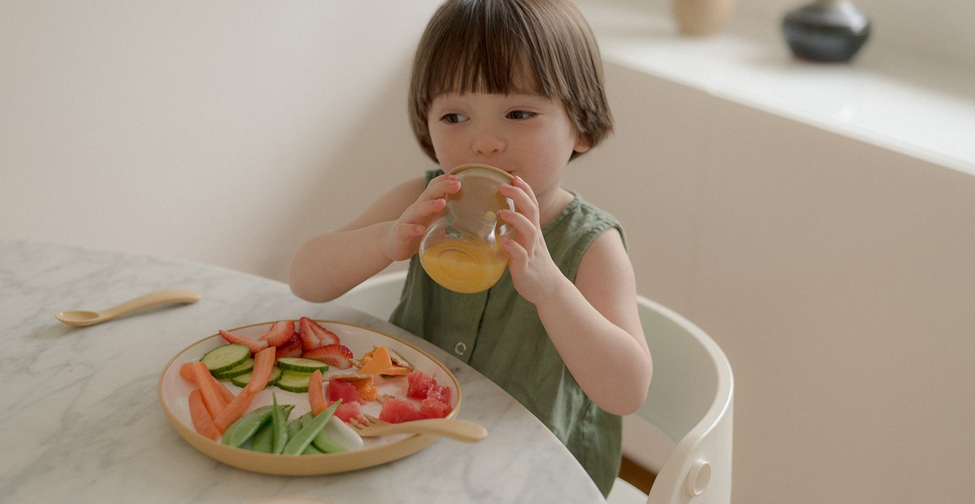 Toddler drinking out of the BONBO straw cup with BONBO plate filled with fruits and vegetables