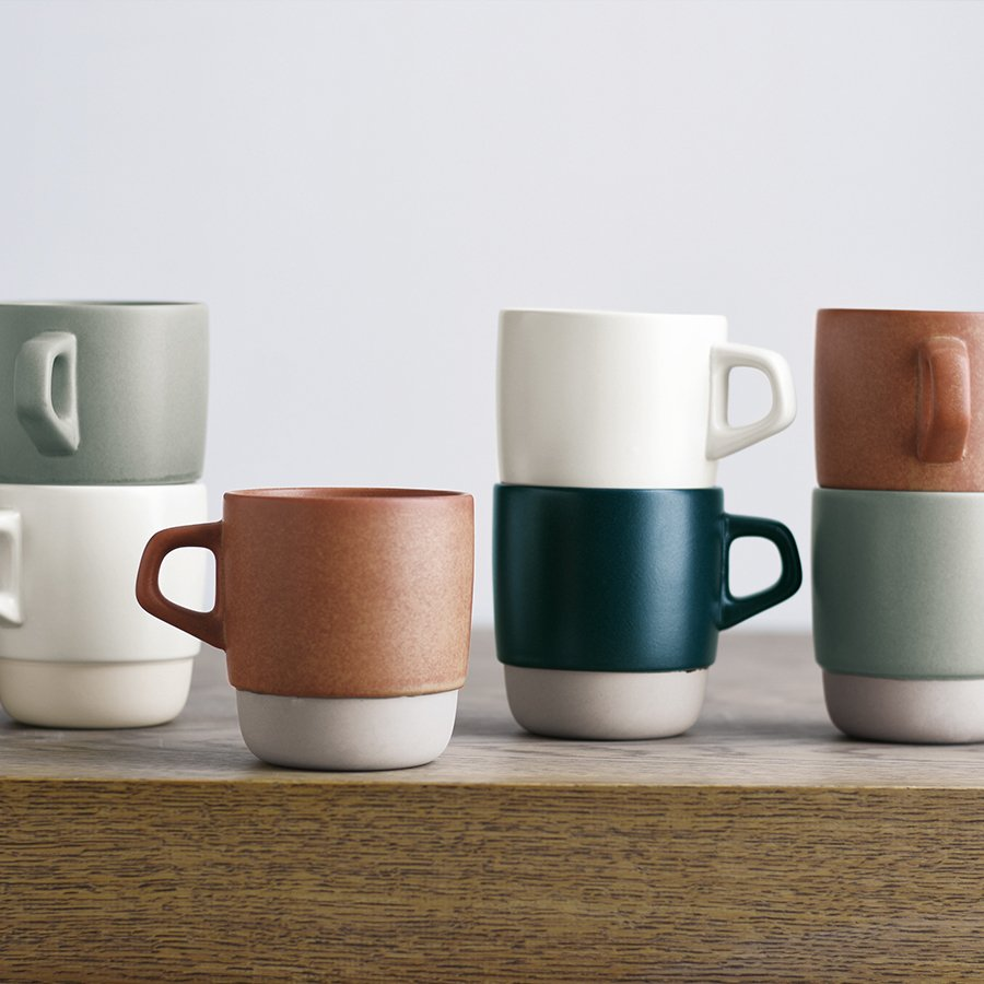 SCS stacking mugs in gray, orange, white, and navy