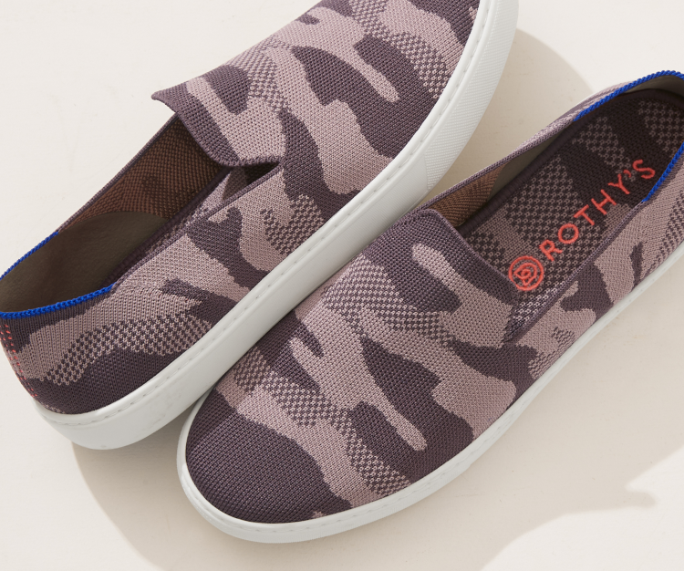 Close up of a pair of The Sneaker in Taupe Camo, shown from the top against a cream background.