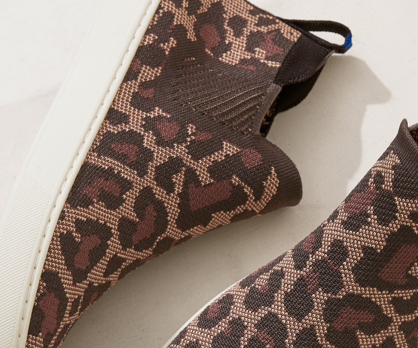 Close up of The Chelsea boot in Wildcat, shown from the top and on its side against a cream background.