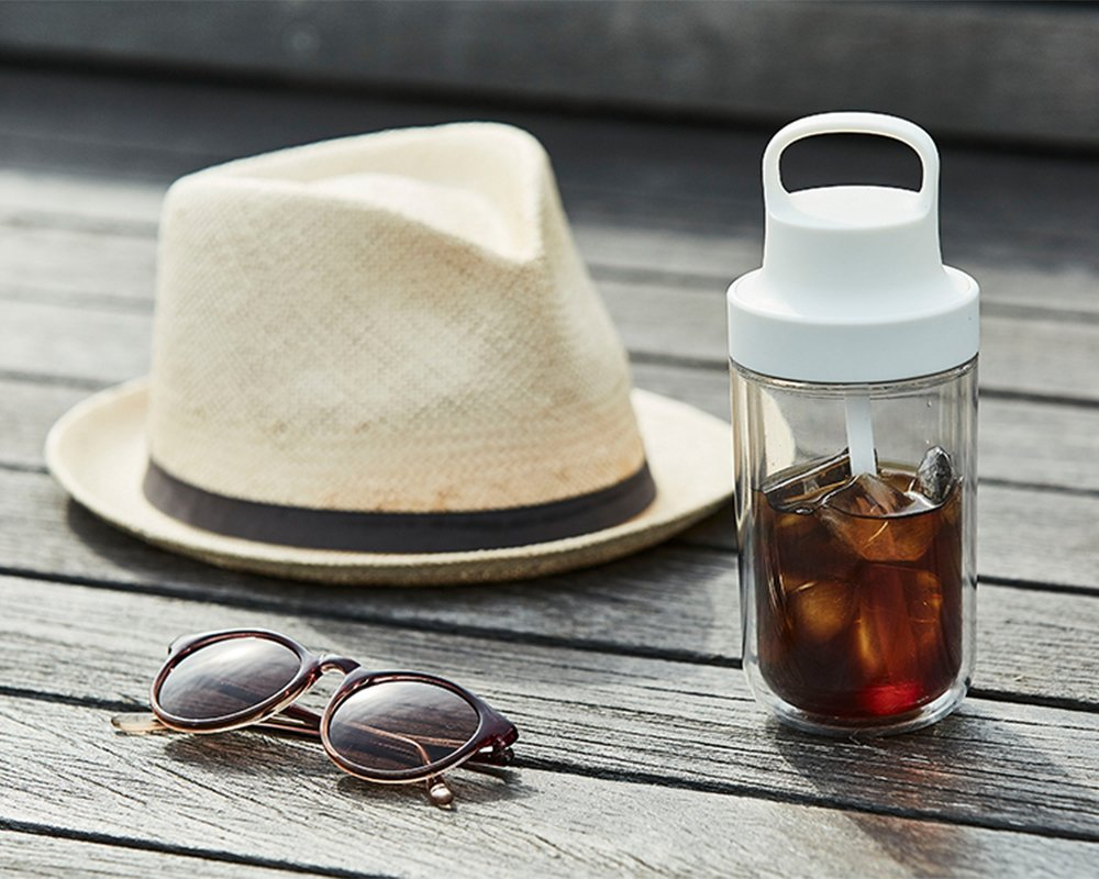 TO GO bottle 360ml in white next to sunglasses and hat