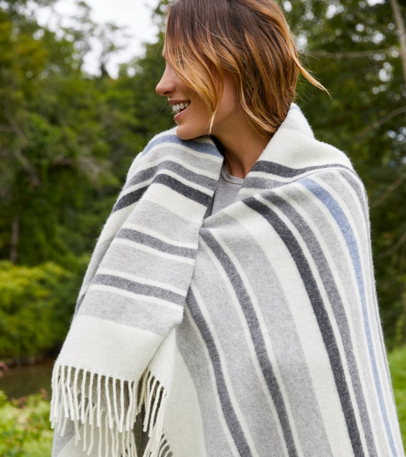 Woman keeping warm with a white, grey, and light blue striped throw blanket draped over her shoulders