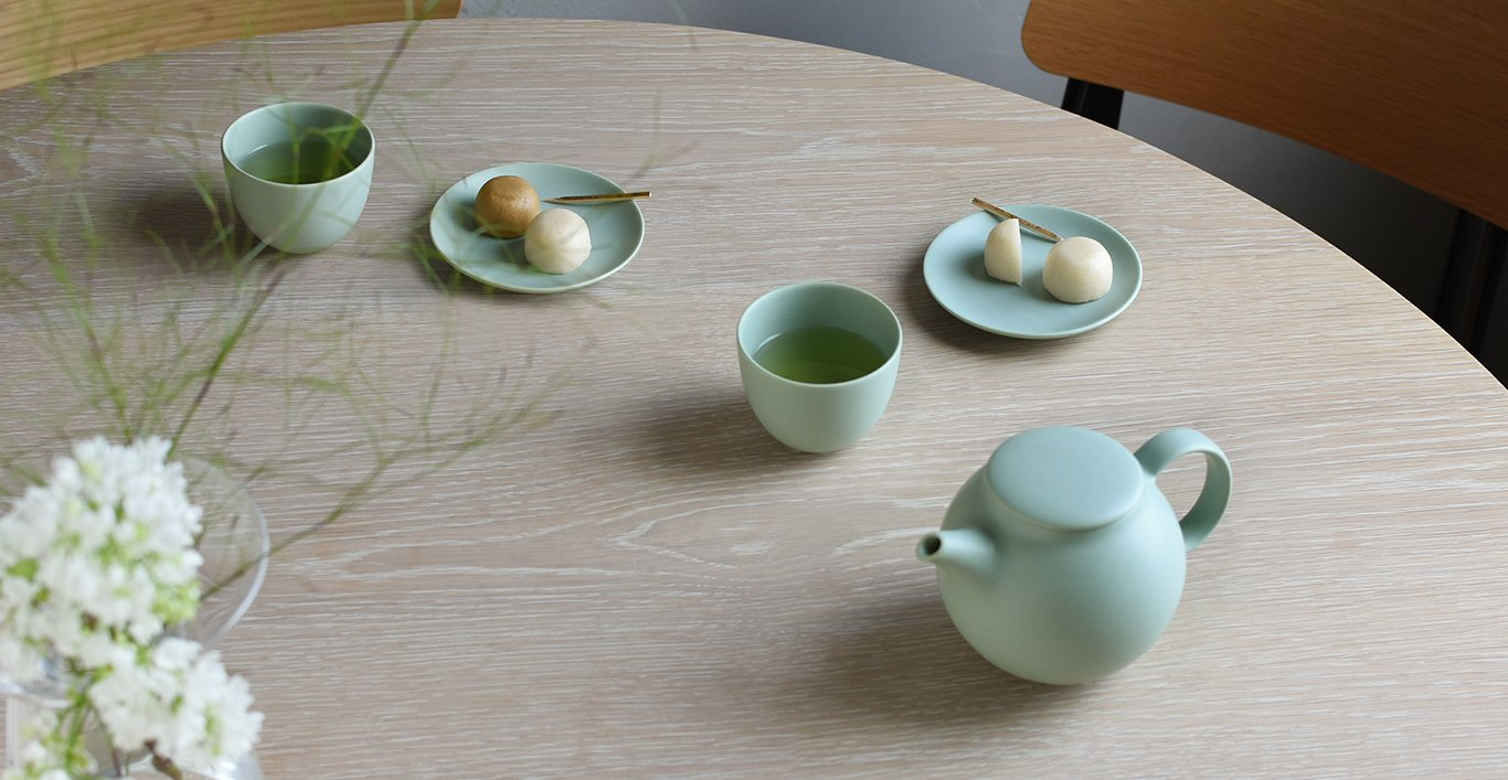 PEBBLE teapot and cup and saucer in moss green on a table