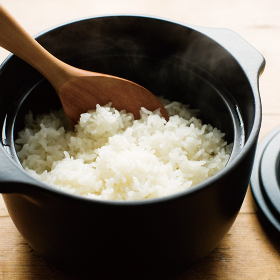 KAKOMI rice cooker black with cooked rice and wooden spoon