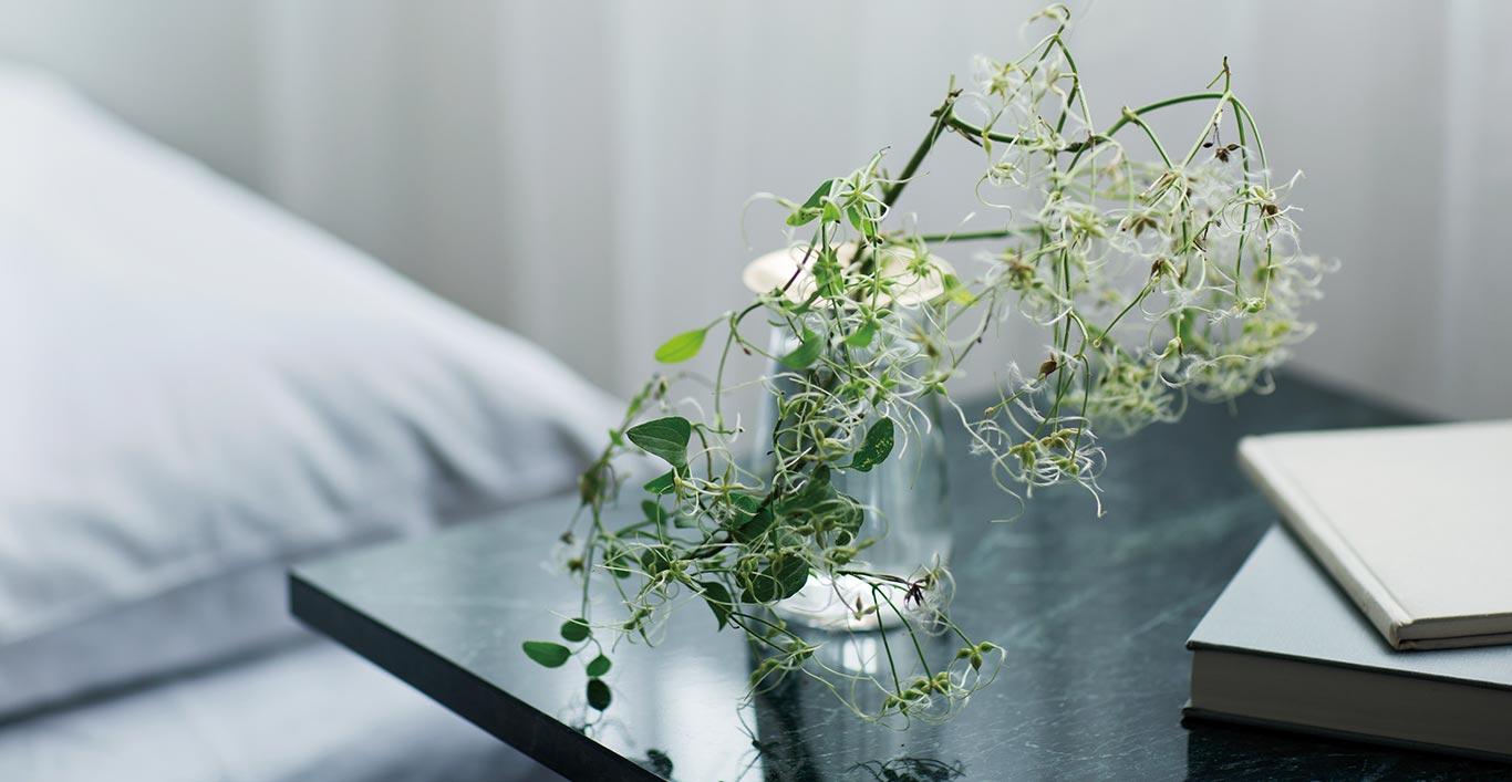 Clear LUNA vase sitting on a marble bedside table