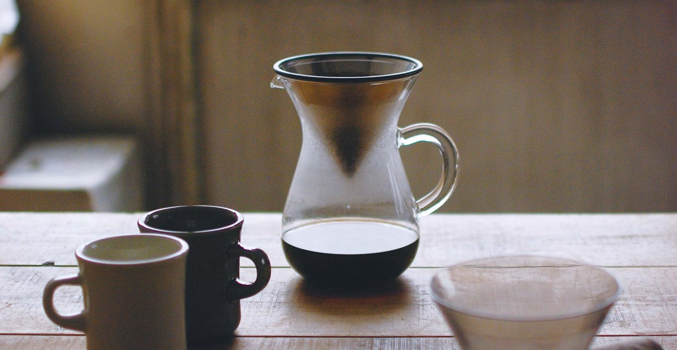 SCS coffee carafe and the SCS mug in blue and gray on a wooden table