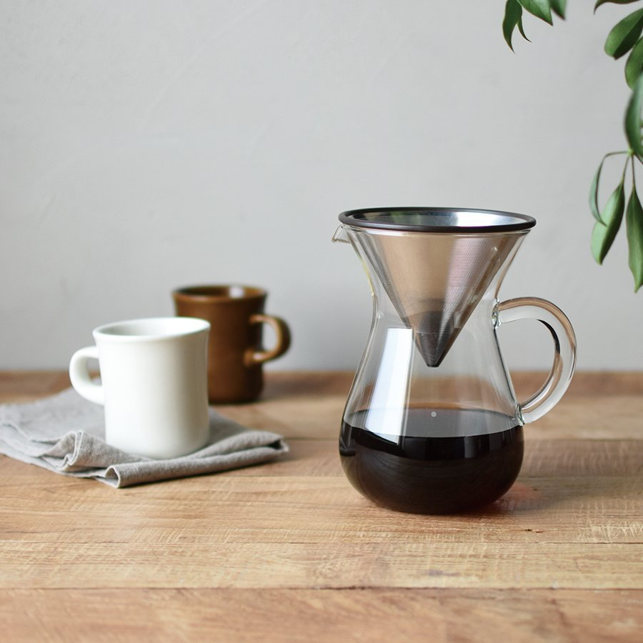 SCS coffee carafe with SCS mug in brown and the SCS mug in white on a gray cloth