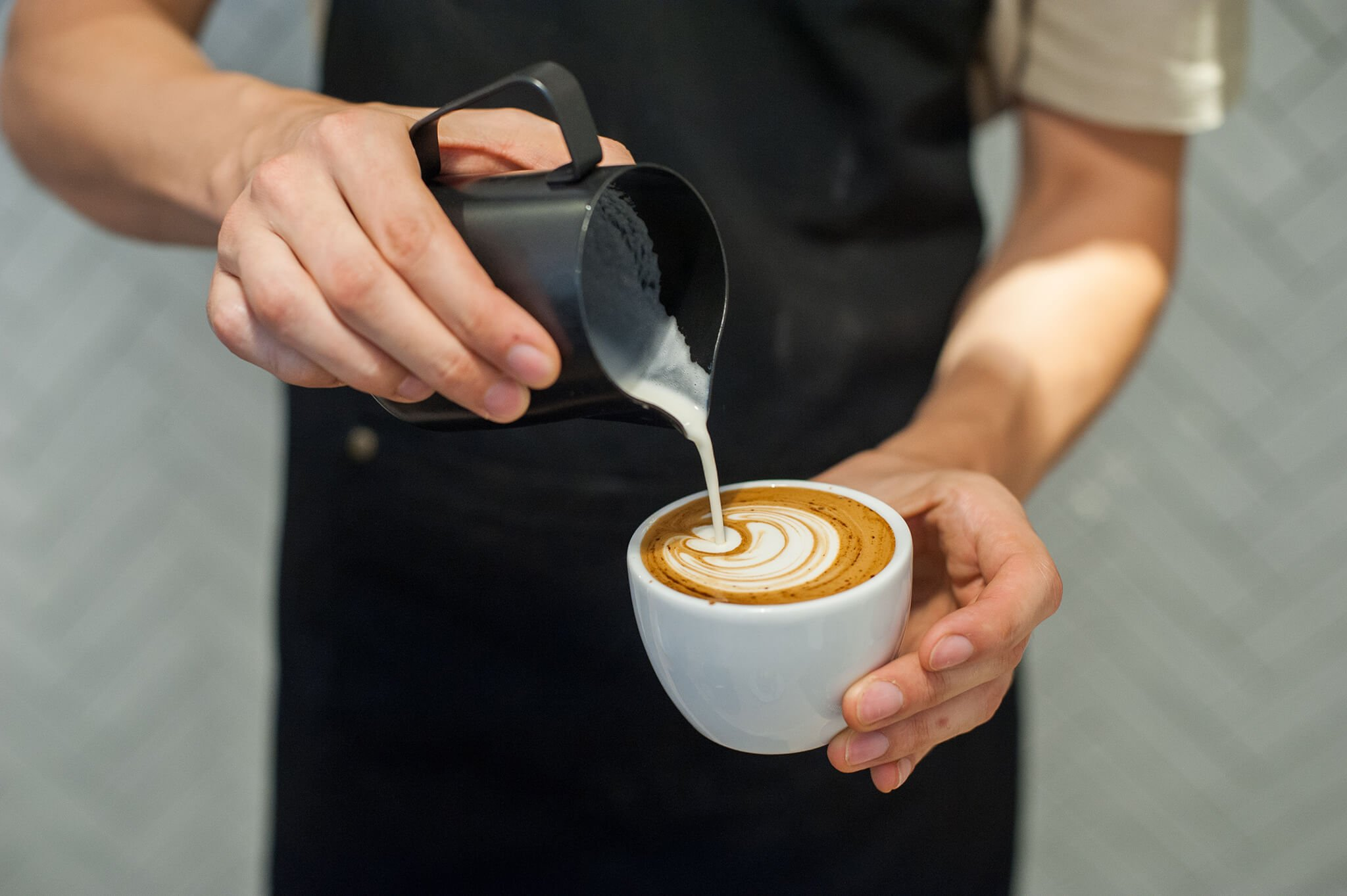Latte art being poured at a coffee making class