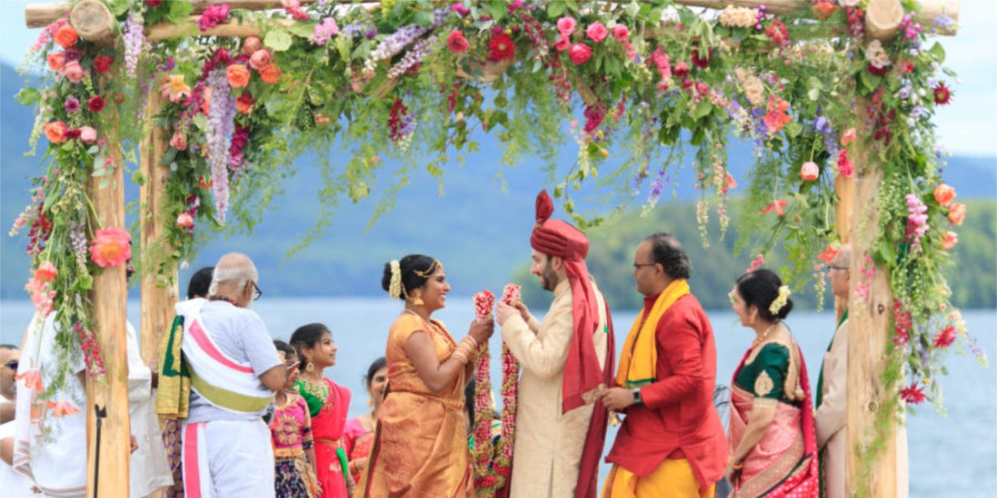 A wedding in front of a lake, a chuppah with vibrant colors flowers and a couple very happy