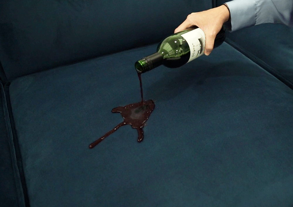 Red Wine being poured onto the seat cushion of teal velvet sofa to demonstrate stain resistance