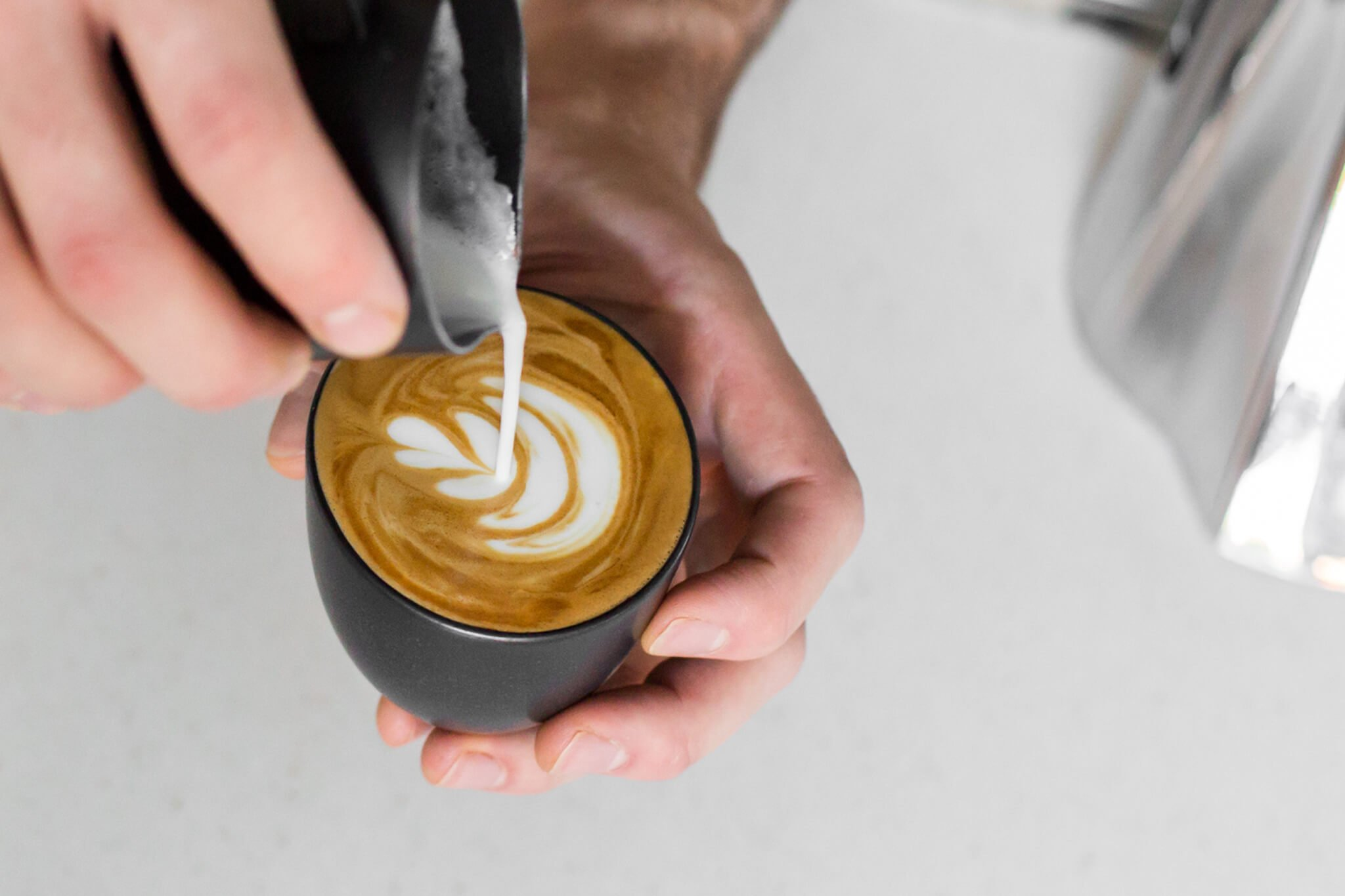 Latte art being poured into a cup