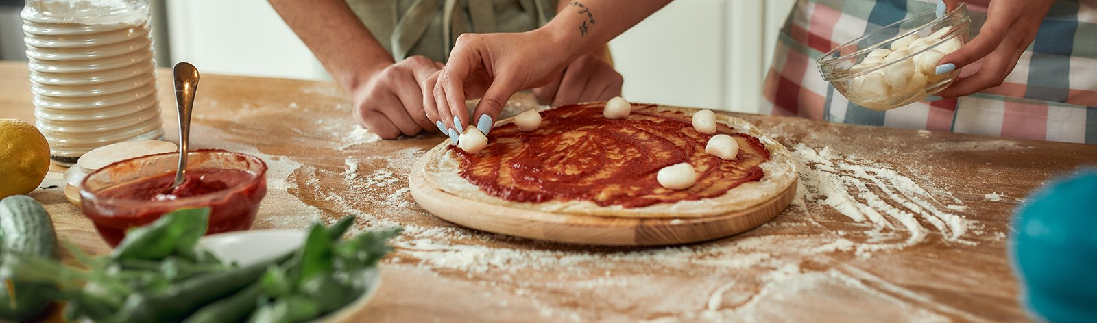Couple making pizza together at home