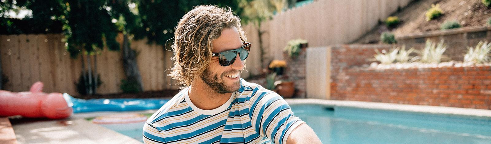 Man wearing Knockaround Torrey Pines sunglasses by the pool