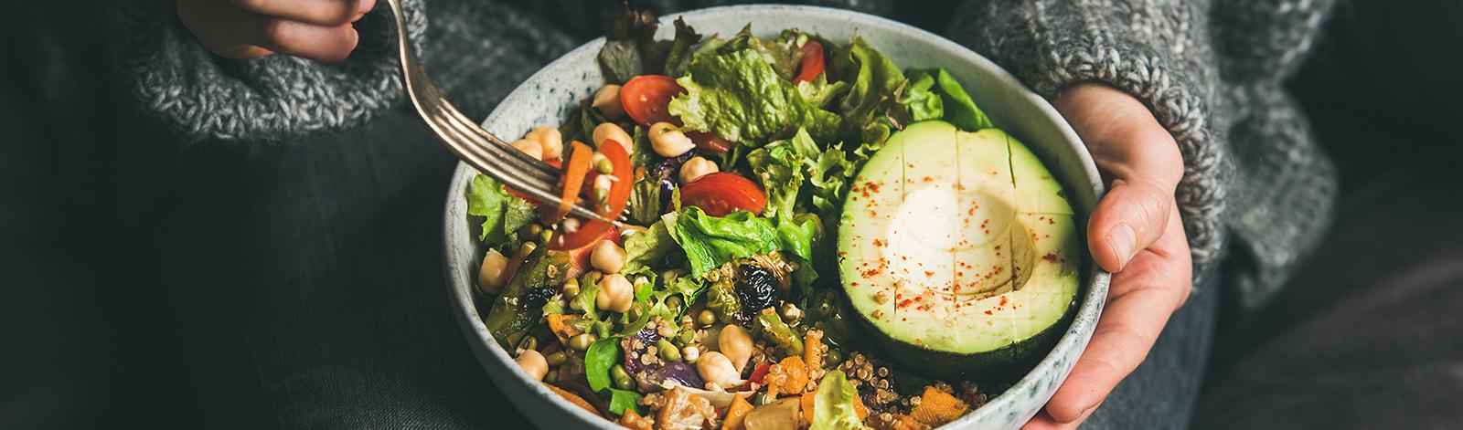 Woman eating a healthy salad bowl