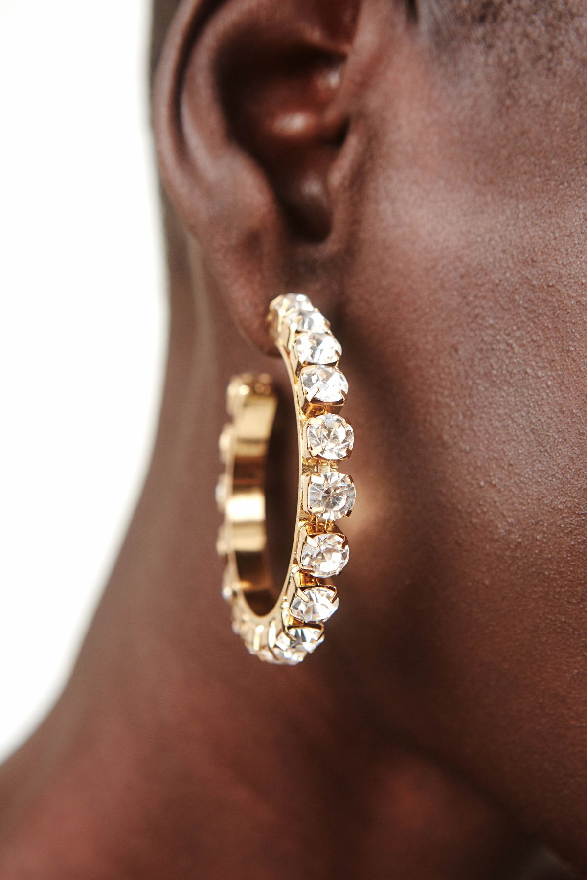 2-inch classic gold round hoop earrings crafted of polished brass set with shimmering oversized white Preciosa crystals. Imported.