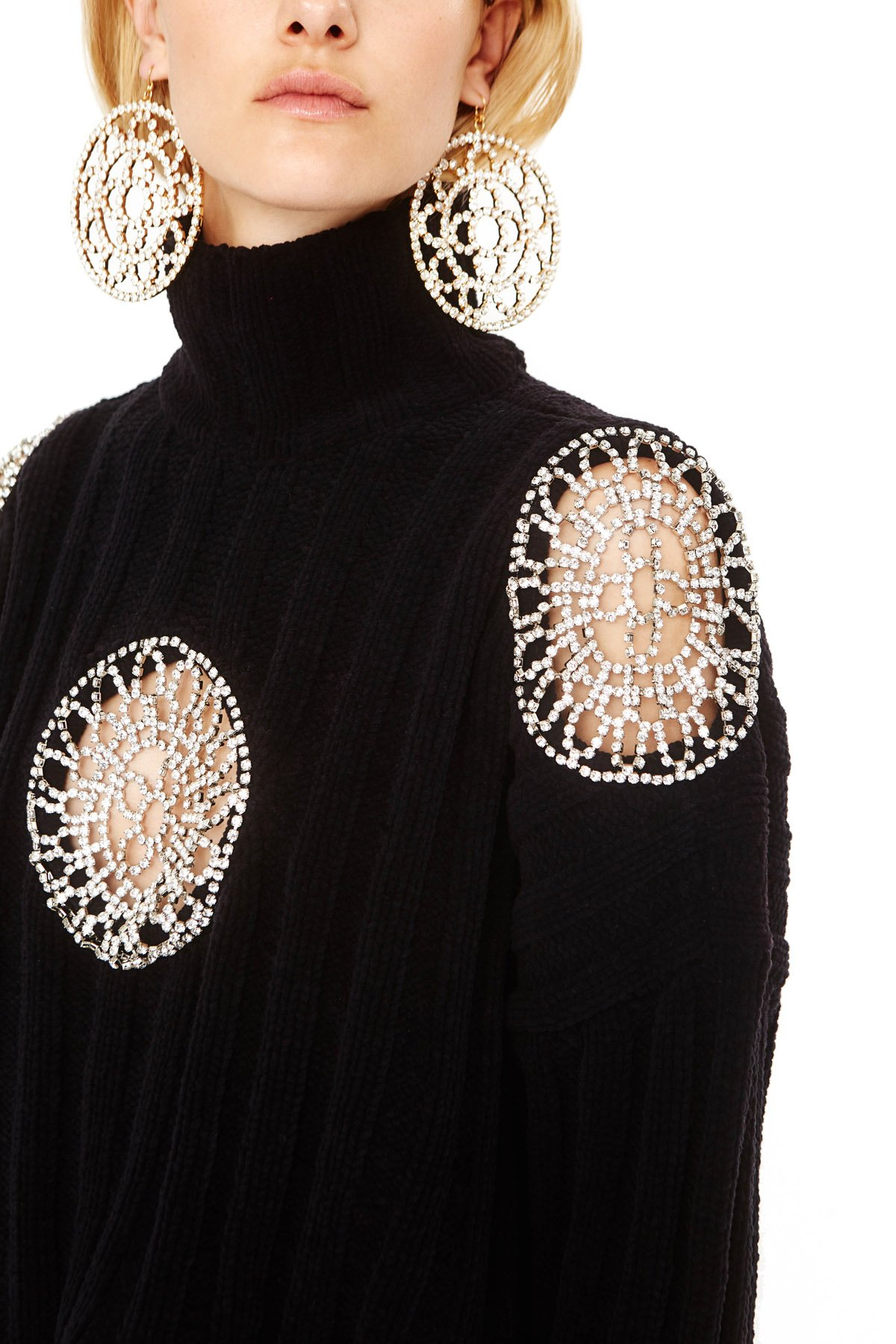 Knitted sweater in an oversized fit. Features clear crystal doily inserts on chest and shoulders. Available in Black.