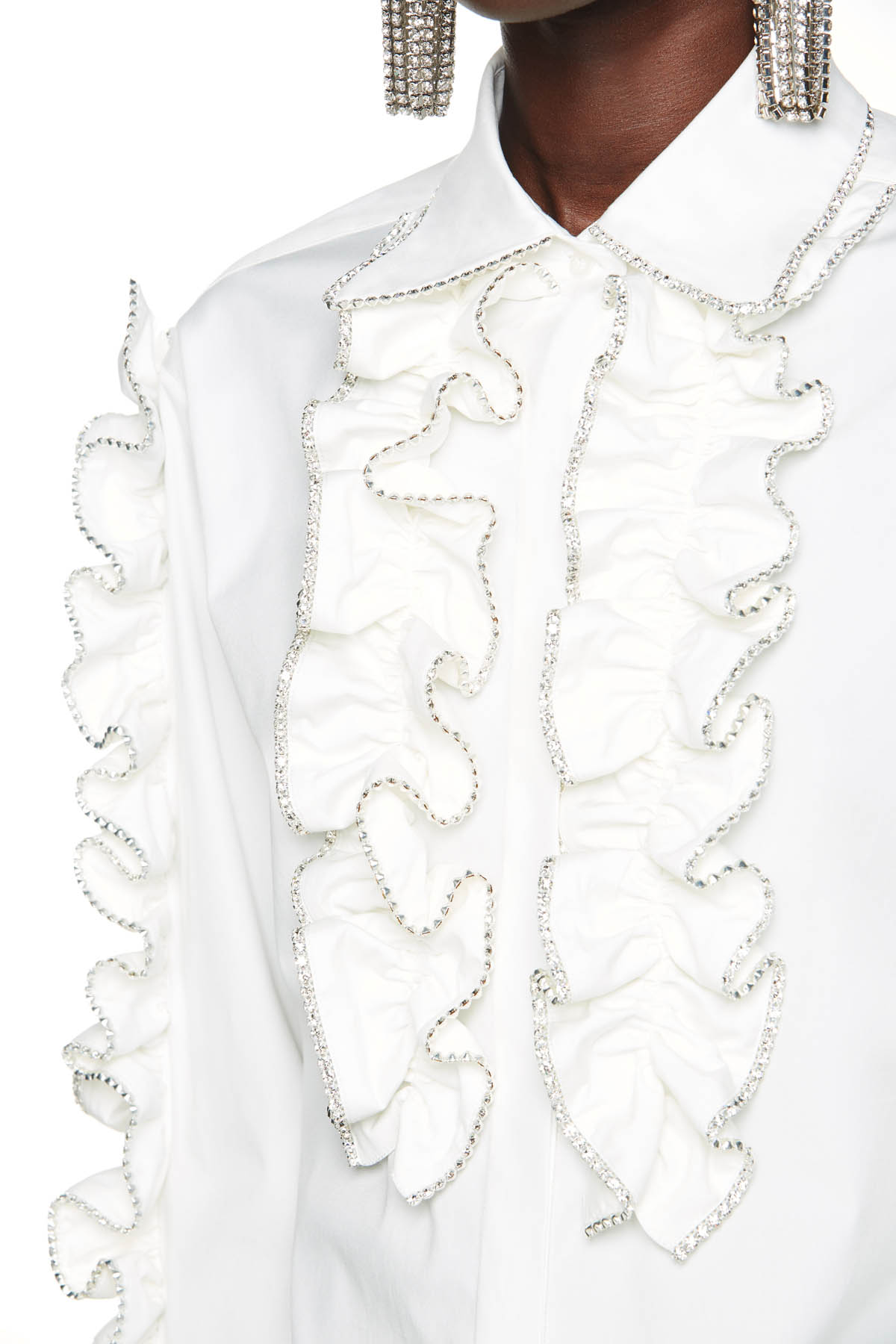 Tailored long sleeve with crystal trim and ruffle detail. Available in white.