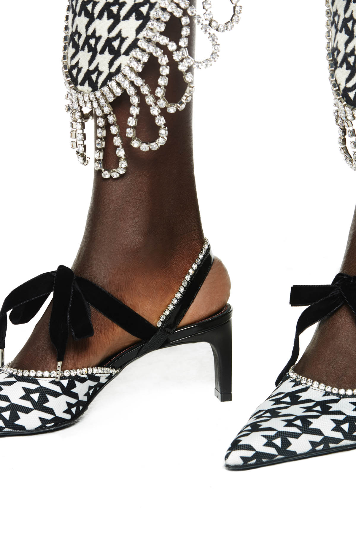 Pointed toe kitten heel with velvet tie closure and crystal trim. 65MM heel. Available in houndstooth.
