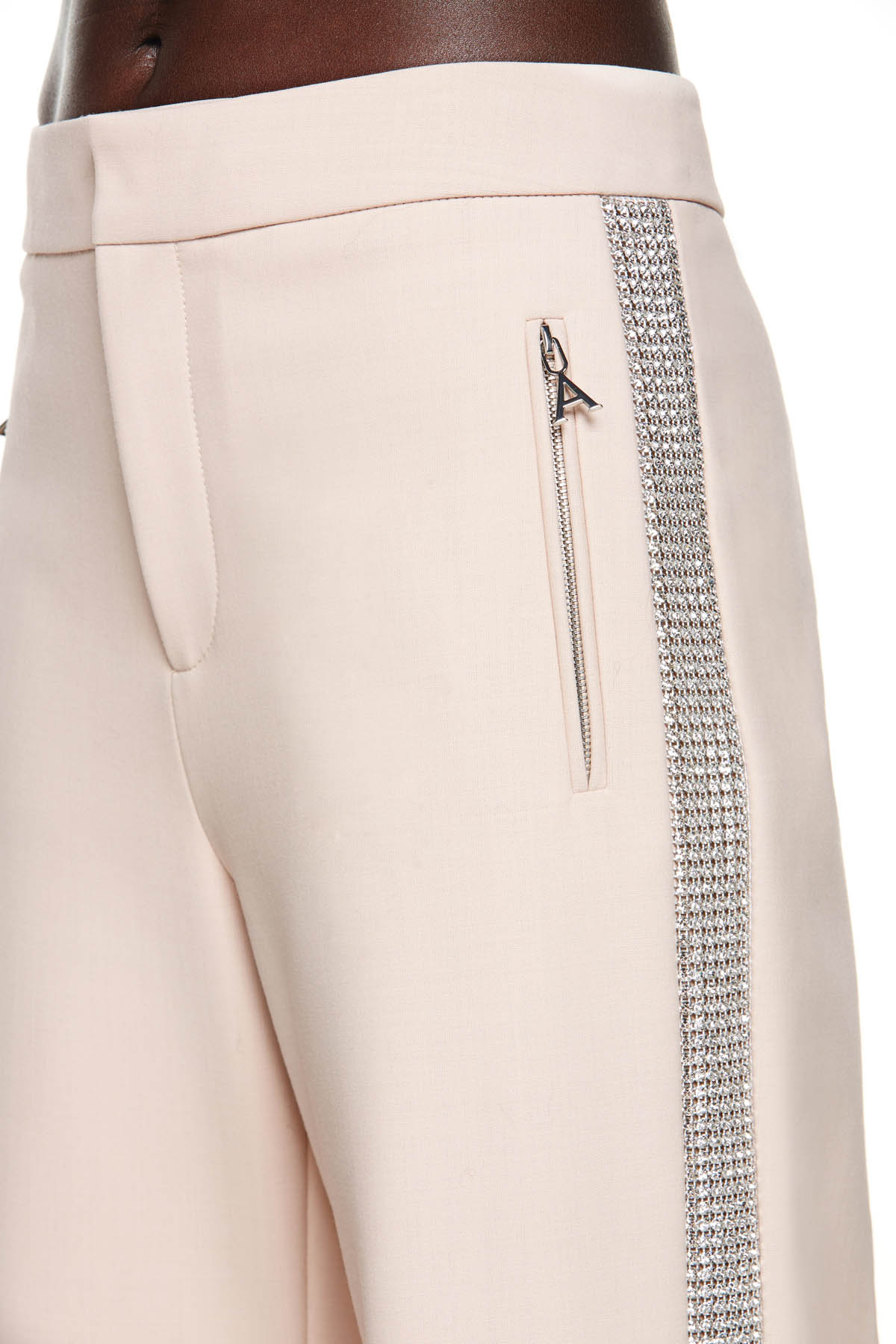 "Tailored wide leg track pant featuring crystal trim stripe embellishment. Features side zip pockets with classic ""A"" logo pull. Available in Blush."
