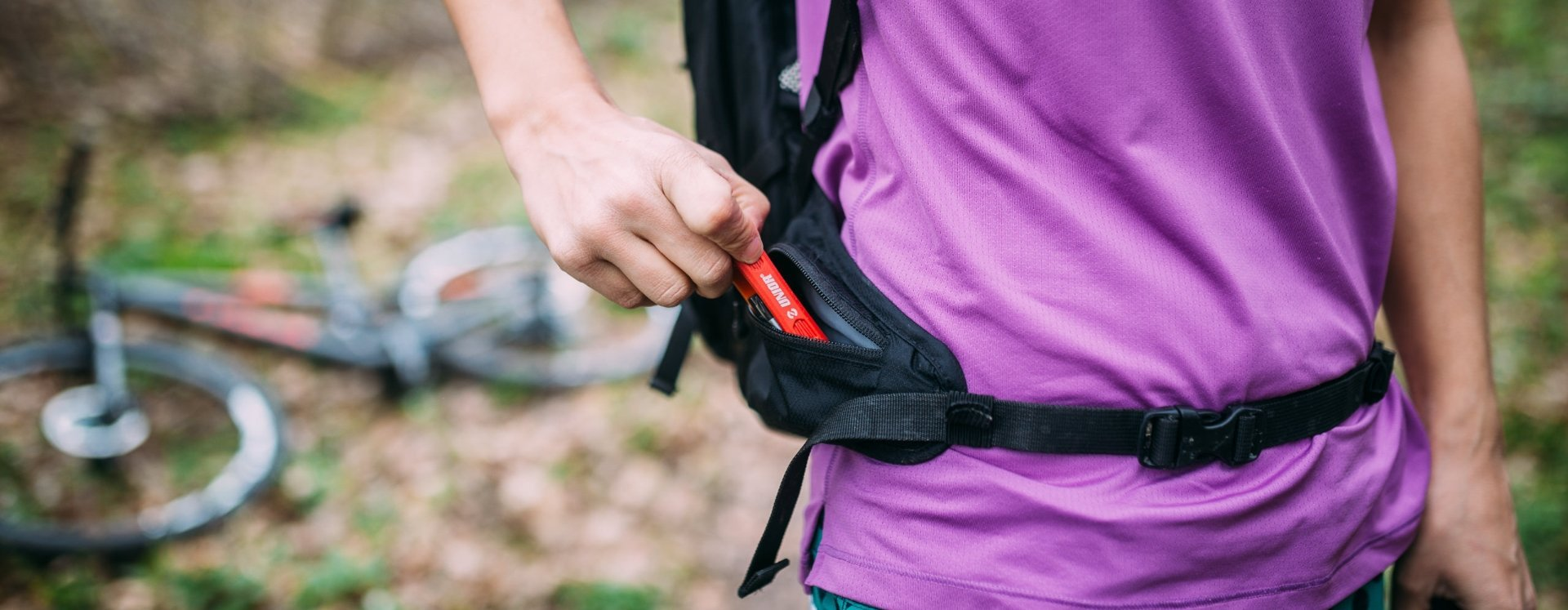 A woman pulls a Unior multitool from her backpack pocket