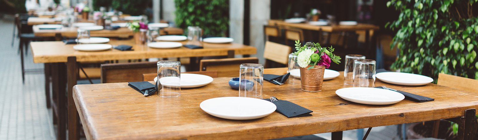 Dishes on the wooden table in outdoor restaurant