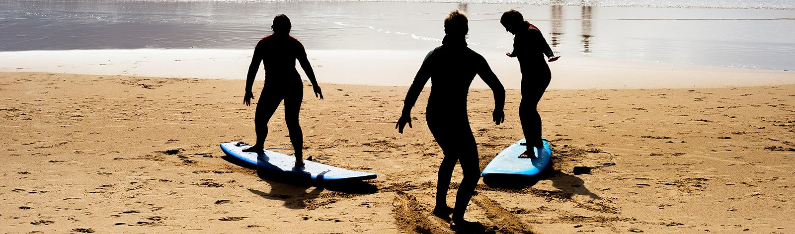 People learning to surf on the beach