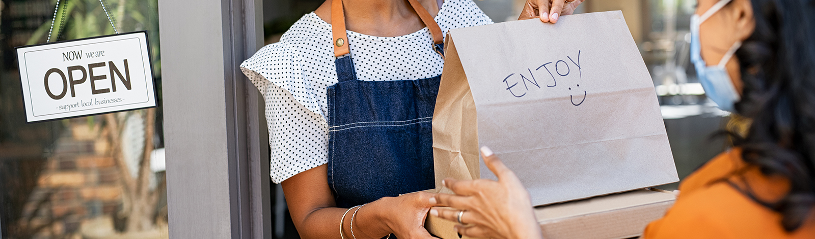 Woman wearing a mask delivering takeout food