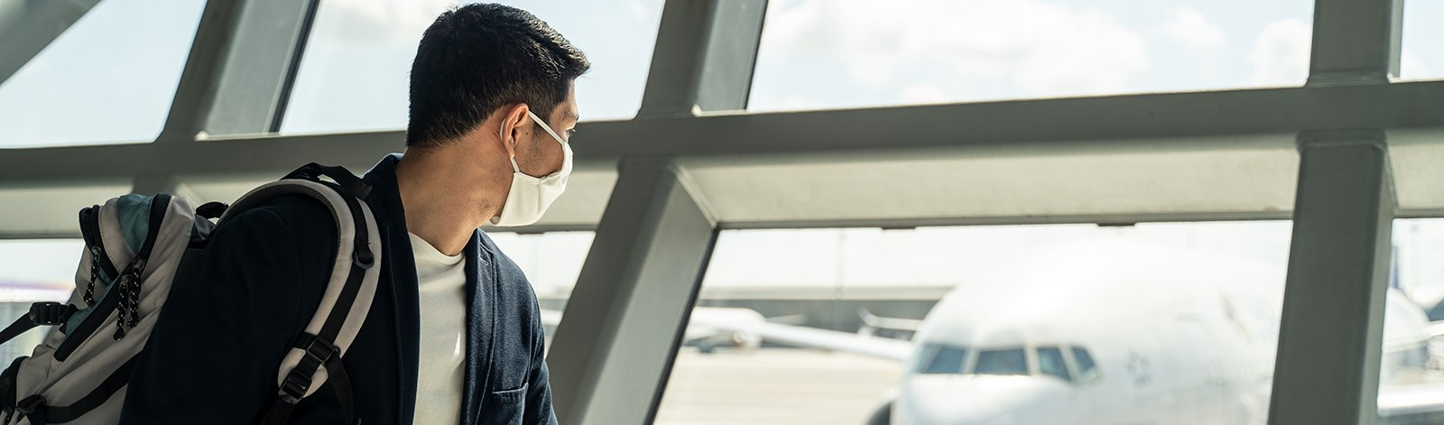 Man wearing a mask at the airport while looking at a plane