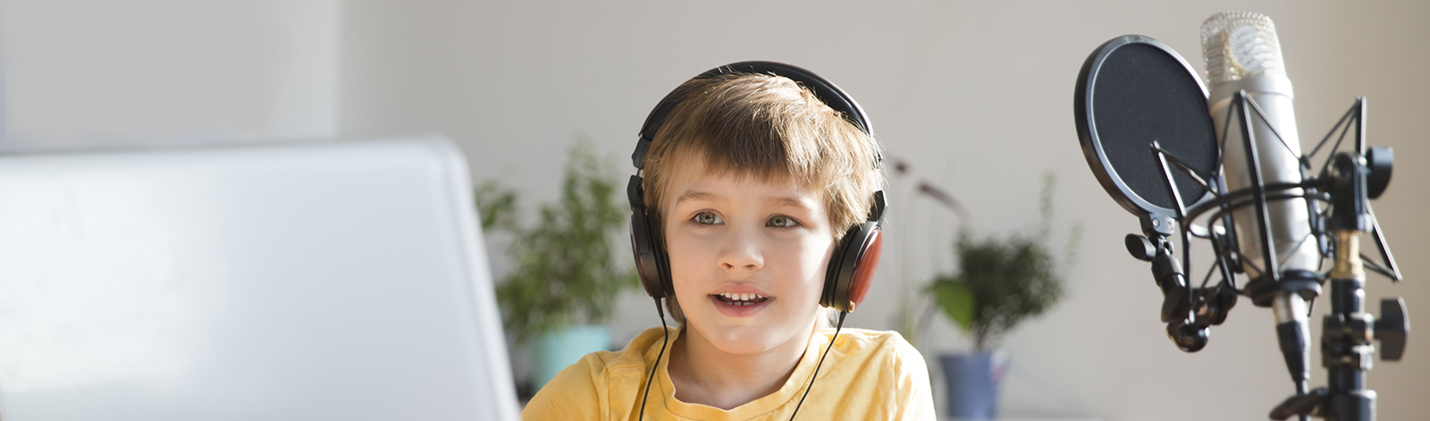 Young boy listening with headphones next to podcast equipment