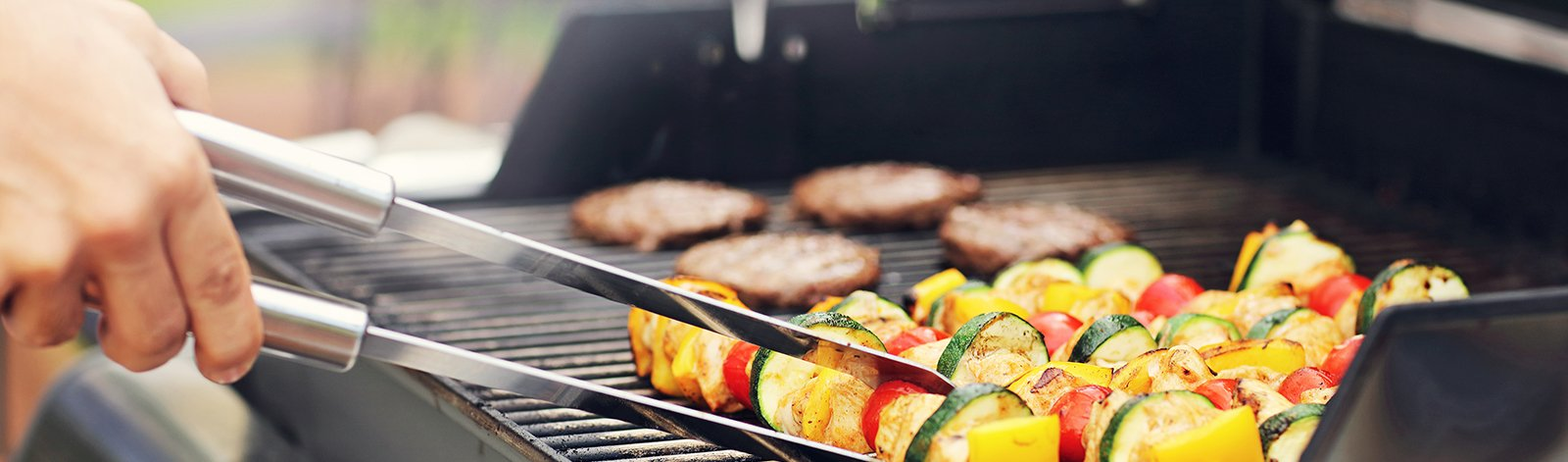 Vegetable skewers and burgers on the grill