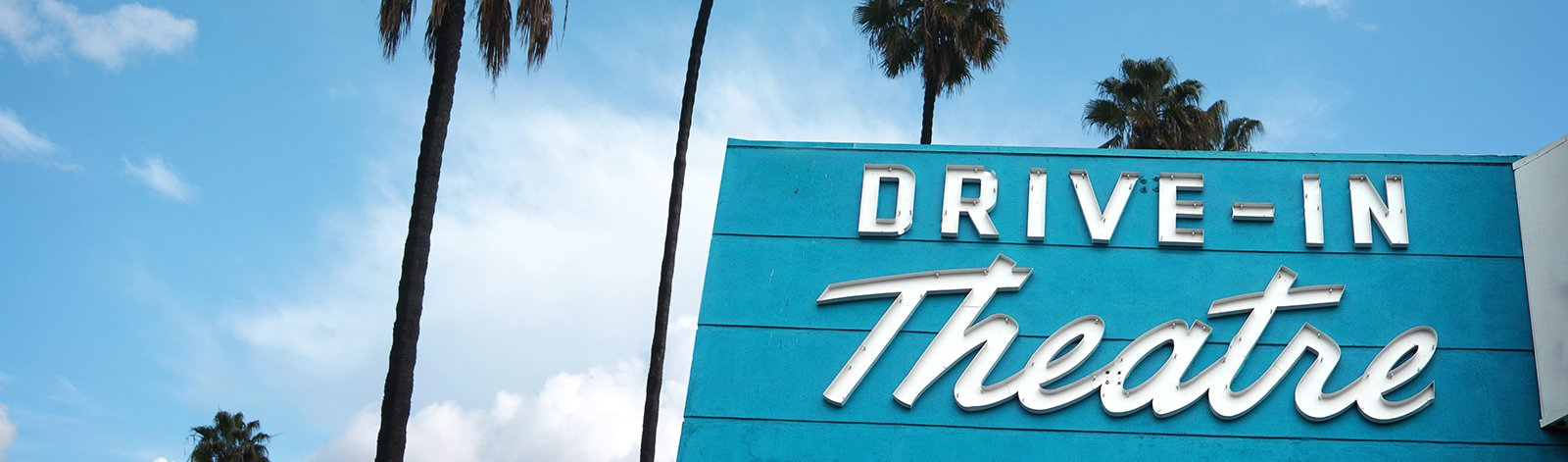 Drive-in theatre sign with palm trees