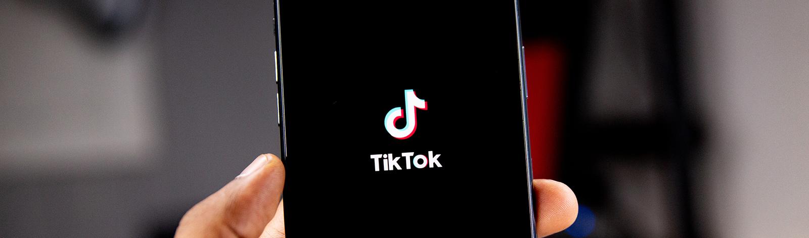 Hand holding smartphone with the TikTok app