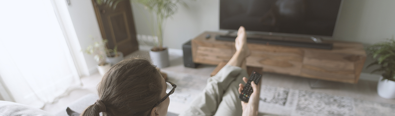 Woman sitting on the sofa and watching TV