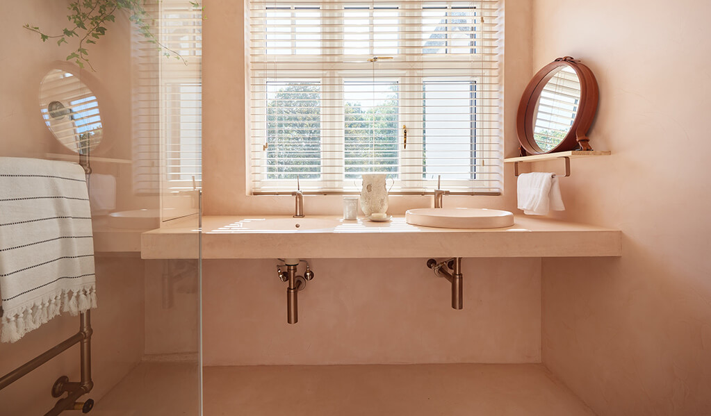 Ade and Lindas Blush pink home bathroom, showing two basins at different heights with a gorgeous big window looking out.