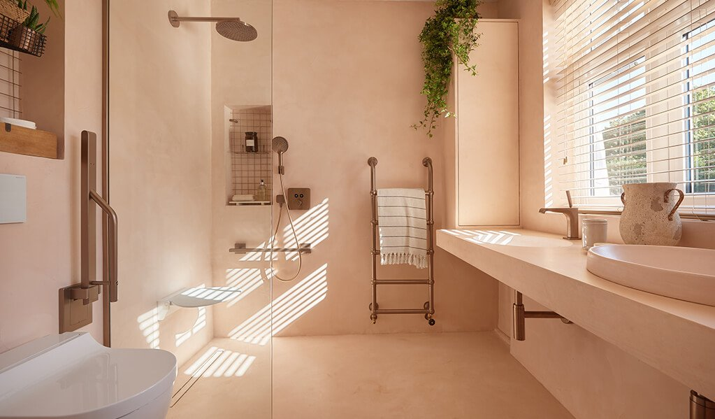 Ade and Lindas Blush pink home bathroom, showing the whole bathroom, flooring and walls are the same tone of blush pink with a rose gold Doc M pack.