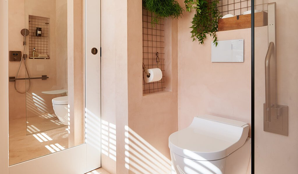 Ade and Linda's blush pink home bathroom, focusing on the large rectangle toilet mirror which is displayed behind the entrance door.