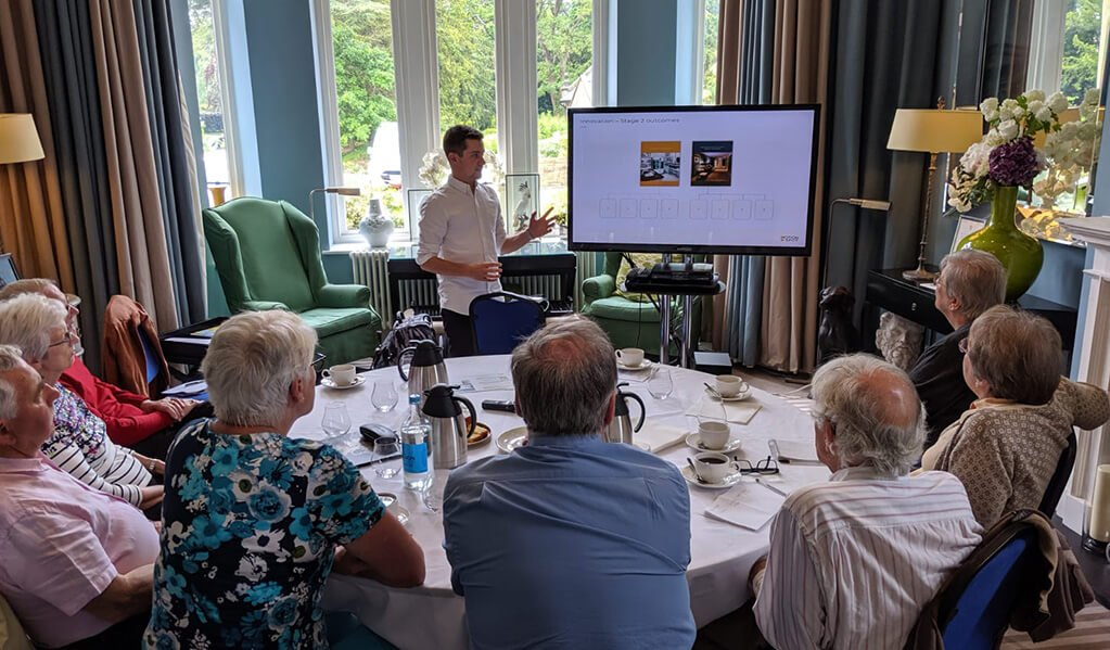 A member of the Motionspot team stood next to an interactive screen showing visual imagery to 8 older people sat around a table who all appear to be engaged.