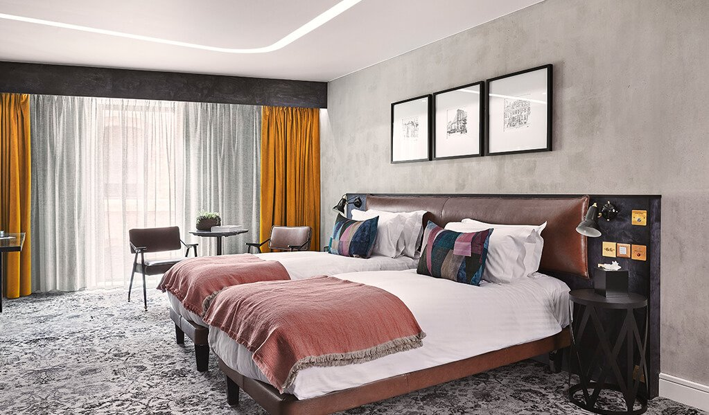 Hotel Brooklyn bedroom, Lovely large windows with mustard curtains with a table and chairs to admire the view. Blush details run throughout the soft furnishings with two single zip together beds which sit on a patterned carpet.