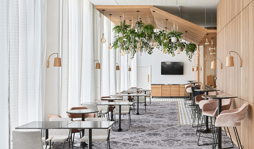 Hotel Brooklyn dining area, beautiful vertical light wood panelling running across the ceiling as well as adjacent to the floor to ceiling windows. Complimented with light wood wall lights and ceiling hung plantation with exposed bulbs.