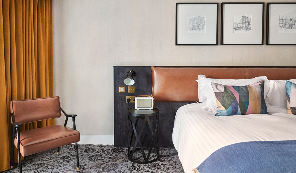Hotel Brooklyn bedroom, zoomed in snap of chocolate coloured leather headboard and black transferable bedside tables showcasing the lovely brass detailed switches and sockets.