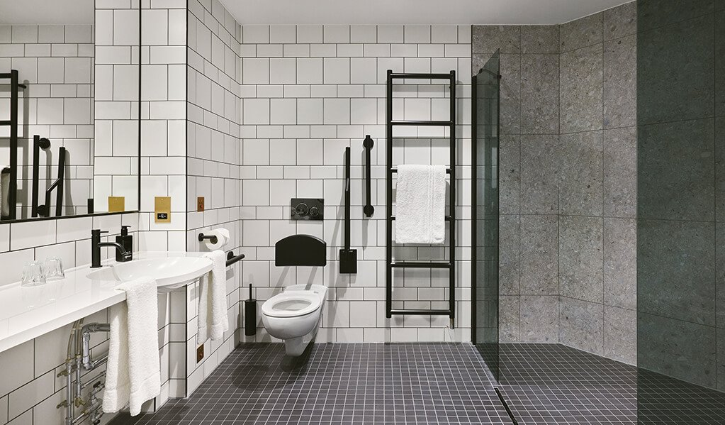 Hotel Brooklyn bathroom, white wall tiles with black tile trims, matt black finishes throughout the bathroom with black tinted shower glass. Beautiful contrasting tiles for shower area with smaller tiled contrasting floor.