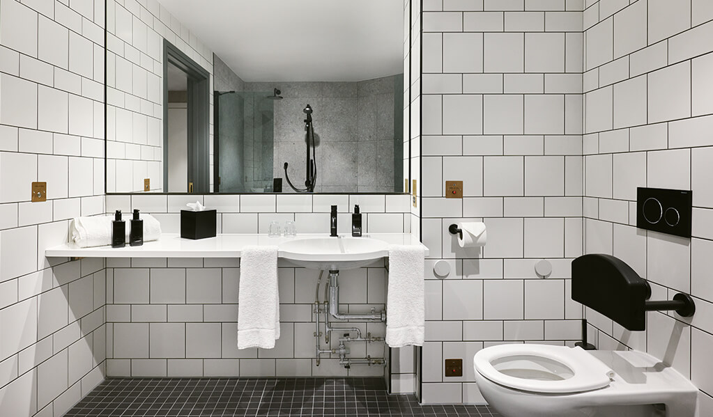 Hotel Brooklyn bathroom, clean white wall tiles with black tile trims, matt black finishes with matching accessories. Beautiful statement square mirror which sits above the vanity, leaving a stylish touch to an already modern accessible bathroom.